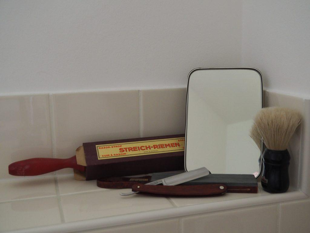 Ein Rasiermasser, ein Streichriemen, ein Wetzstein, ein Rasierpinsel und ein Spiegel auf einer gefliesten Fläche im Bad. Infos, Tests, Preise, Vergleiche. Sinnbild für das Thema der Seite.